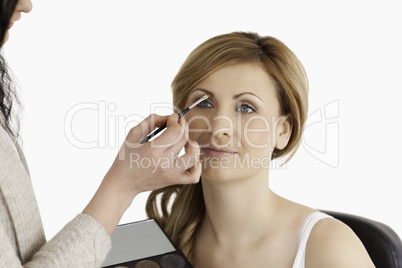 Make-up artist applying make up to a cute woman