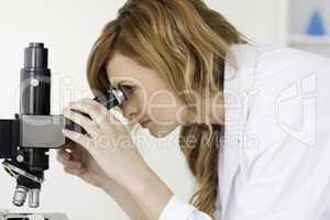 Attractive blond-haired scientist looking through a microscope