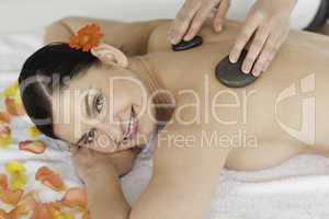 Attractive dark-haired woman enjoying the procedure of massage