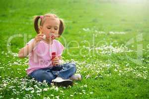 Little girl is sitting on green meadow