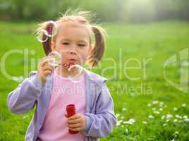 Little girl blows soap bubbles on meadow
