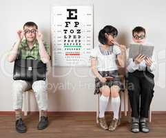 three person wearing spectacles in an office at the doctor
