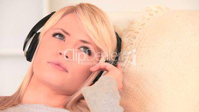 junge Frau sitzt auf der Couch und hört Musik
