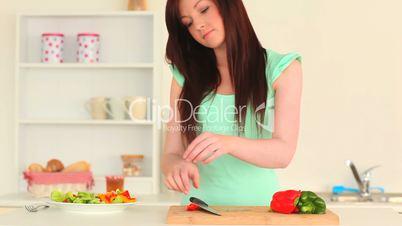junge Frau schneidet Gemüse für Salat