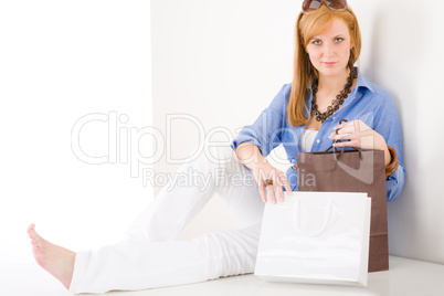 Shopping young woman with paper bag sitting