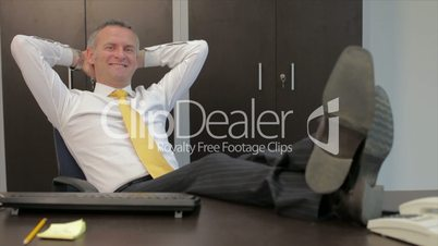 Happy relaxed businessman smiling in office