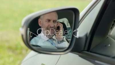 Businessman calling on mobile phone in car