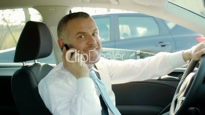Businessman calling with cell phone in car
