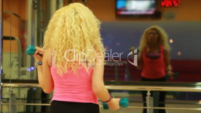 girl using dumbles in a gym