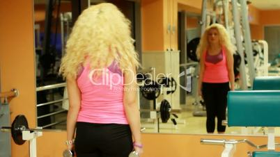 girl using dumbles in a gym 3