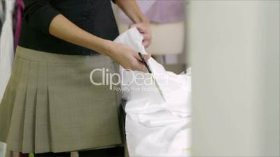 Young hispanic female dressmaker cutting white fabric for bridal gown and smiling at camera
