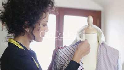 Woman working ad tailor in fashion design studio