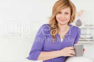 Beautiful red-haired woman holding a cup of coffee while sitting