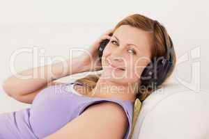 Beautiful blond-haired woman listening to music lying on the sof