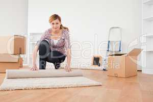 Pretty blonde woman rolling up a carpet to prepare to move house