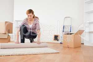 Lovely woman rolling up a carpet to prepare to move house