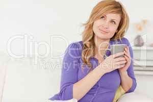 Pretty red-haired woman holding a cup of coffee while sitting on