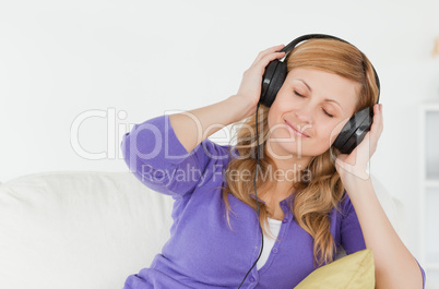 Beautiful red-haired woman listening to music and enjoying the m