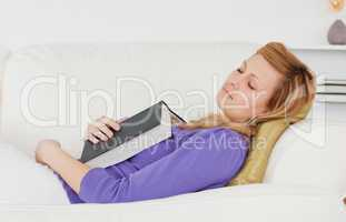 Beautiful woman lying on the sofa who has fallen asleep while re