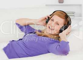 Joyful red-haired woman listening to music