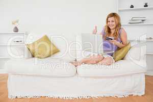 Happy woman sitting on a sofa is going to make a payment on the