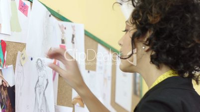 Young hispanic female dressmaker preparing show with models and sketches