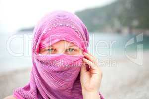 Beautiful girl with face covered by red scarf