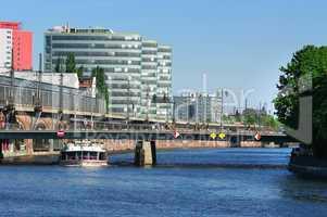 Drei Hochhäuser hintereinander an der Spree mit Brücke und Bahnstrecke
