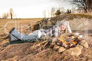 Campfire hiking woman with backpack sleep country