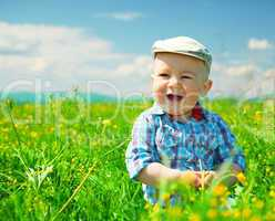 Little boy is playing on green meadow