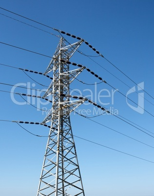 Steel support of overhead power transmission line on sky background