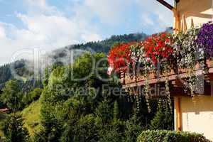 Alpine chalet balcony with flowers on green hills background