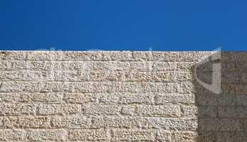 Upward view of beige stone wall