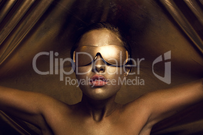 topless gold body painting on a brunette girl with a funky hairstyle