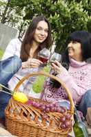 Mother and daughter drinking wine outdoors