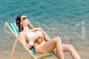 Summer young woman sunbathing in bikini suncream