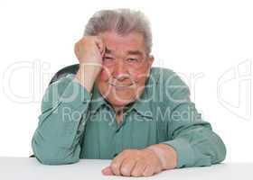 Netter Senior sitzt am Tisch
