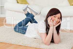 Beautiful red-haired woman posing while lying on a carpet
