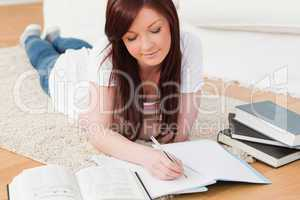 Beautiful joyful red-haired girl studying for while lying on a c