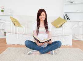 Charming red-haired female reading a book while sitting on a sof