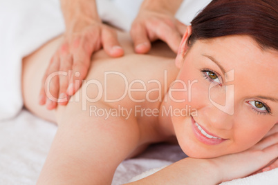 Closeup of a charming red-haired woman receiving a massage in a