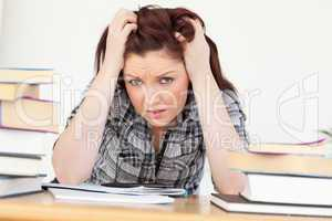 Beautiful red-haired female being upset while studying for an ex