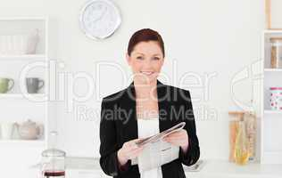 Good looking red-haired woman in suit reading the newspaper in t