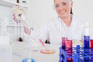 Gorgeous red-haired scientist using a pipette