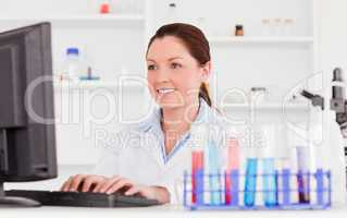Red-haired scientist typing a report with her computer