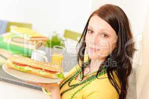 Young student girl eat sandwich in kitchen