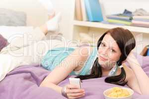 Young student girl on bed hold phone