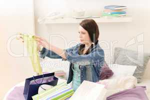 Young happy student girl unpack shopping bags