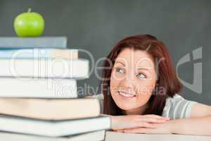 Young student looking at the apple on the top of her books