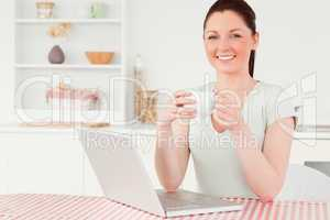 Attractive woman relaxing on her laptop while drinking a cup of